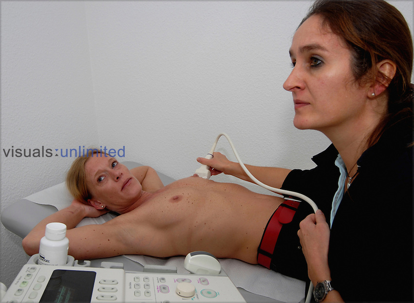 Woman having a breast sonogram examination by a female doctor