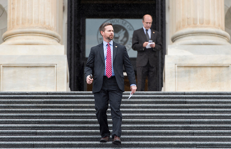 UNITED STATES - NOVEMBER 19: Rep. Rodney Davis, R-Ill., walks down the House steps in the rain as members of Congress head home for the Thanksgiving recess following the final votes on Thursday, Nov. 19, 2015. (Photo By Bill Clark/CQ Roll Call)