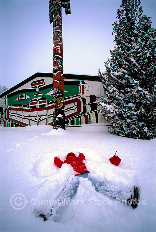 Woman making Snow Angel at Kwakwaka'wakw (formerly Kwakiutl) Style Longhouse and Totem Pole in Thunderbird Park, Victoria, Vancouver Island, British Columbia, Canada, in Winter (Model Released)