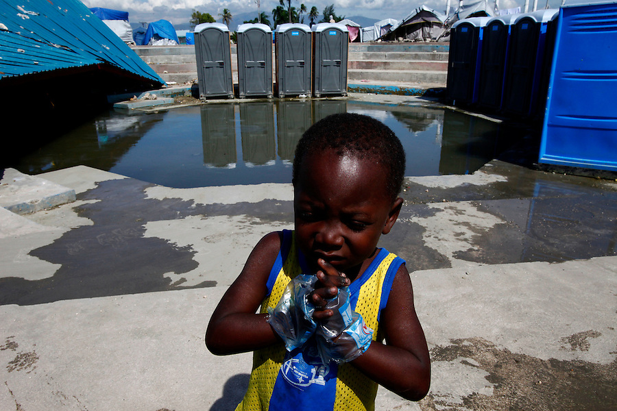 Nov 10, 2010 - Port-au-Prince, Haiti.A young residents of a tent city in the Cite Soleil area of Port-au-Prince, Haiti wears water bags as gloves in an effort, his older sisiter said, to avoid getting cholera, as other residents gather water from pipes just yards from portable toilets and flood waters from Hurricane Tomas Wednesday, November 10, 2010 as fears of a Cholera outbreak spread through the area just two days after cases of the infection were confirmed in the area, the poorest slum in Haiti's capital. Officials from the Pan American Health Organization warn that Haiti's cholera epidemic, spread primarily through consuming infected water and food, is likely to grow much larger in the wake of Hurricane Tomas.  (Credit Image: Brian Blanco/ZUMA Press)