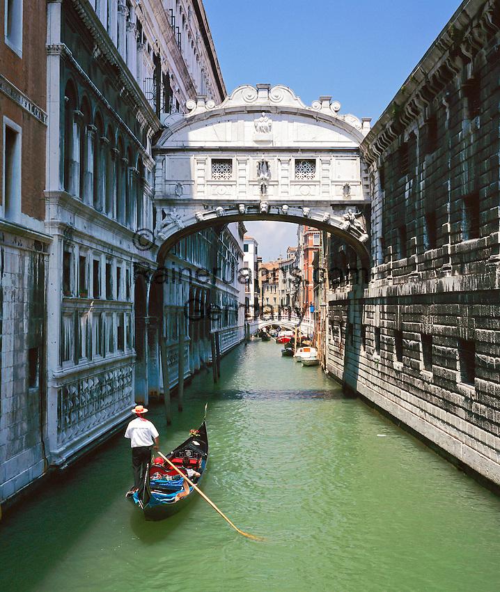 Italy,  Veneto, Venice: Gondolier along side canal | Italien, Venetien, Venedig: Gondoliere in traditioneller Kleidung faehrt Touristen in einer Gondel durch die Kanaele der Stadt