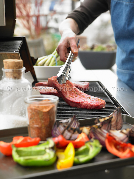 Steaks being placed on a gas grill, with a tray of grilled vegetables in foreground.