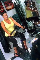 Woman eight months pregnant on exercise bike.