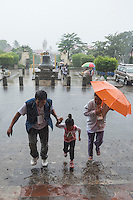 People running towards the local Church at the Historical Town of Taal during a heavy tropical Rain storm, Philippines