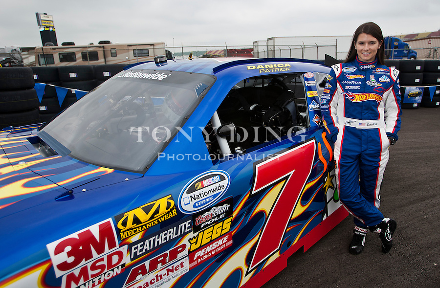 Danica Patrick poses for pictures with her new Hot Wheels NASCAR racecar, featuring its iconic red and orange flames, Thursday, Aug. 12, 2010, at Michigan International Speedway in Brooklyn, Mich. Hot Wheels debutes its sponsored racecar, in a new format for the NASCAR Nationwide Series, at this weekend's CARFAX 250 Nationwide race. (Tony Ding/ AP Images for Mattel, Inc.)