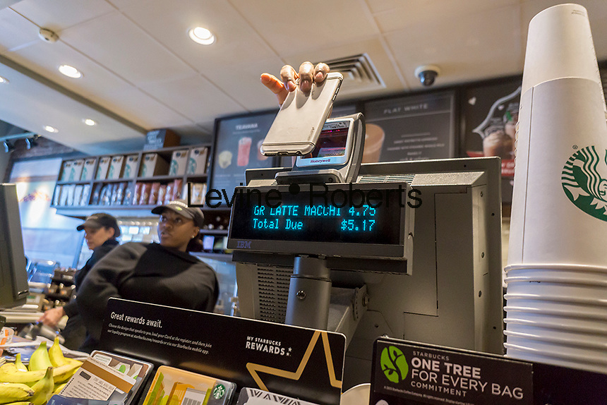An employee assists a customer in paying with Apple Pay on her iPhone in a busy Starbucks in Queens in New York on Saturday, February 13, 2016.  (© Richard B. Levine)
