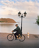 GREECE, Patmos, Skala, Dodecanese Island, an elderly man rides his bicycle past the Taverna Tzivaeri along the Agean Sea