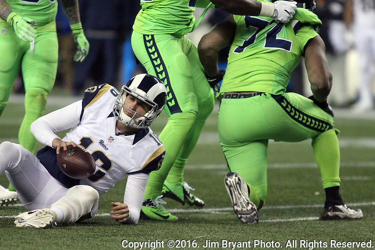 Los Angeles Rams quarterback Jared Goff (16) gets up after being sacked for a loss by Seattle Seahawks defensive end Michael Bennett (72) at CenturyLink Field in Seattle, Washington on December 15, 2016.  The Seahawks beat the Rams 24-3.  ©2016. Jim Bryant Photo. All Rights Reserved