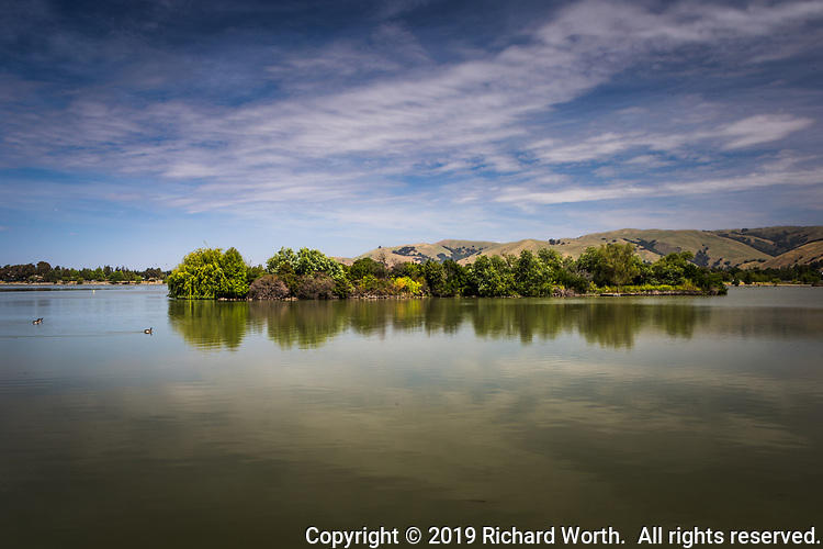 Duck Island and its reflection, in the southeast section of Fremont, California's Elizabeth Lake, under a cloud streaked sky on a quiet spring afternoon.