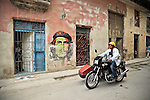 HAVANA - JANUARY 3: A man on a motorbike rides past a building with Che Guevara graffiti drawn on it in Havana, Cuba.