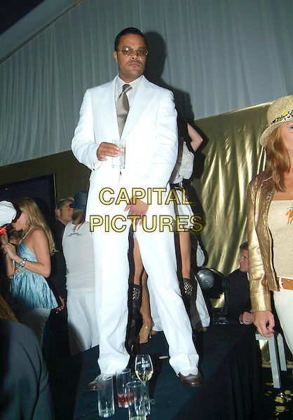 GUEST.Attends Naomi Campbell's Le Carnival D'Or Party, Palm Beach, during the 58th International Cannes Film Festival, Cannes, France, May 19th 2005..full length white suit sunglasses standing on table drink.Ref: KRA.www.capitalpictures.com.sales@capitalpictures.com.©Persun/Capital Pictures
