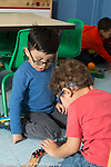 Preschool 3 year olds two boys playing together with train set both wearing glasses