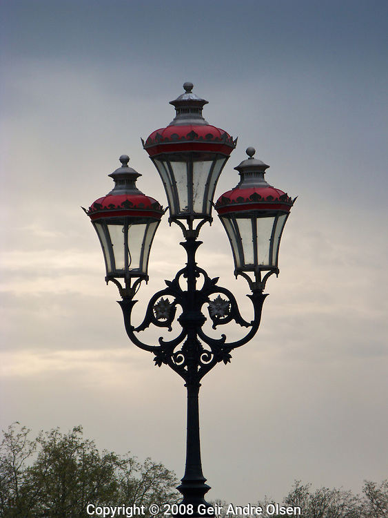 An old street light with three lamps on a bridge in London, UK