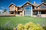 a large, lodge like estate sized home sits under a summer blue sky with a lawn of perfectly manicured green grass fronted by a curved border of mixed annuals, perennials and shrubs