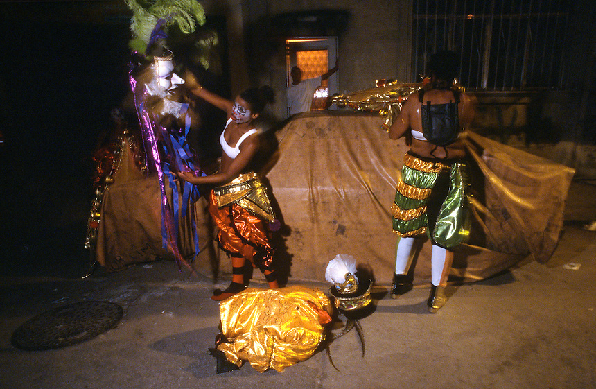 ?In front of an equally disguised car, carnival dancers remove and pack costumes worn during Rio's noted parades. A year's work leads up to a short 90 minutes in the stadium spotlights, after which most of the costumes and floats land in street-side trash heaps.