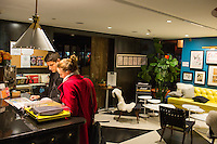 "Metodi and Marisa (in red) Dinolov, of Santa Cruz, Calif., check in after arriving at the hotel from Boston Logan Airport at The Verb Hotel in the Fenway neighborhood of Boston, Massachusetts, USA, on Friday, Dec. 4, 2015. The hotel is considered a ""boutique hotel"" and has collections on display throughout the premises of music memorabilia from the Boston area."