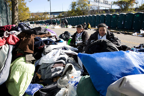 Volunteers and independent contractors help gather discarded clothing and other trash littering the Athletes Village where runners waited and prepared for the start of the ING New York City Marathon on Staten Island on 07 November 2010.