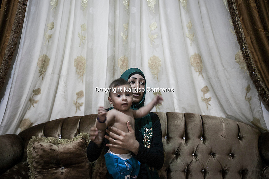 June 09, 2015 - Beirut, Lebanon: Doua, the daughter of Ammal Akkar (not pictured) and her grandson Hamza, a Palestinian refugee family, pose for photo at their home in Shatila refugee camp. (Photo/Narciso Contreras)
