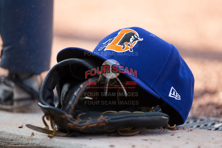 A Durham Bulls hat sits on top of a glove in the home dugout during the game against the Louisville Bats at Durham Bulls Athletic Park on August 9, 2015 in Durham, North Carolina.  The Bulls defeated the Bats 9-0.  (Brian Westerholt/Four Seam Images)