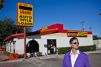 Kelly Griffith of the Center for Economic Integrity poses for portraits in front of an auto title loan business in Tucson Arizona.  The auto title loan industry sprang up in response to Griffith's successful campaign to sunset payday loans.  Griffith claims that the newest incarnation of high-interest loans is predatory by definition because the brokers' business models depend on loan recipients defaulting.