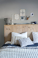 The headboard is made of salvaged scaffolding wood and is used to display a series of objects