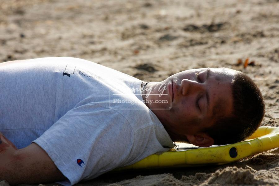 A victim on a backboard injured on a beach