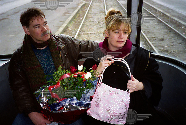 A couple hold a bunch of flowers on a tram in Timisoara.