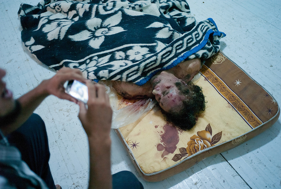 A Libyan man uses a camera phone to photograph the body of Muammar Gaddafi lying in a commercial freezer at the African Tunisian Souq in Misrata, Libya, Saturday October 22, 2011. The confirmed death of Muammar Gaddafi brings closure to an 8 month uprising turned revolutionary war.