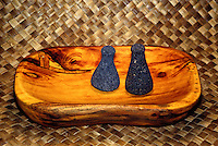 Stone poi pounders rest on a wooden tray placed on a lauhala mat.