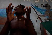 """Atignu, a  """"trokosi"""" religious slave  performs a pagan traditional ritual under the supervision  in one of the shrines of Atito in the Volta region, Ghana on Saturday March 10 2007.."""