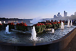 A Water Fountain And Niagara Fall, Canada, In Silhouette On A Clear Morning