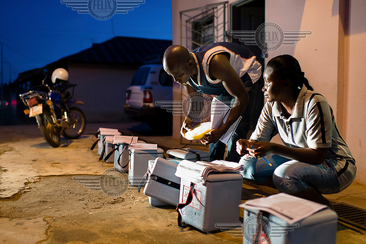 Gideon Kwakye, Disease Control Officer, and Comfort Apenteng, Public Health Nurse, readying vaccines for immunisation teams before dawn during a National Immunisation Days (NID) polio eradication campaign in Achiase.