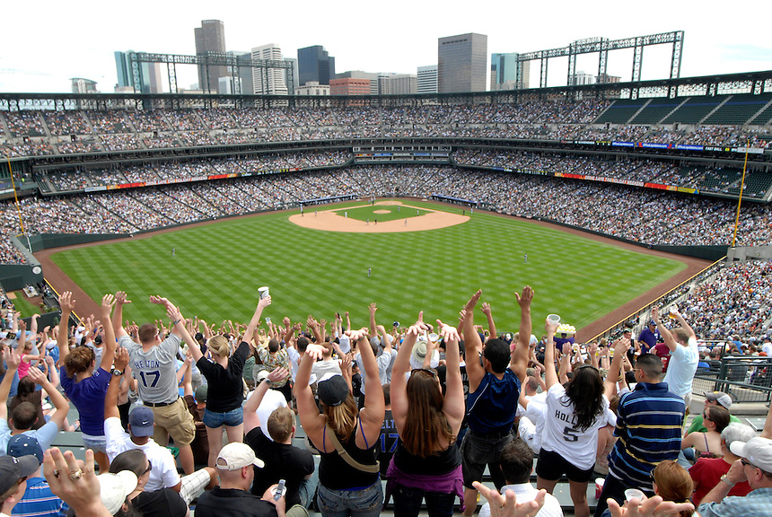 "25 May 2008: Baseball fans raise their arms as ""the wave"" makes its way around Coors Field, during a game between the Colorado Rockies and the New York Mets. The Rockies defeated the Mets 4-1 at Coors Field in Denver, Colorado. FOR EDITORIAL USE ONLY. FOR EDITORIAL USE ONLY"