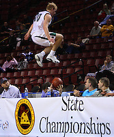 Olympus guard Ray Paull leaps over press row in pursuit of a loose ball. Woods Cross vs. Olympus boys high school Basketball, 4a state tournament at the E Center, West Valley City.