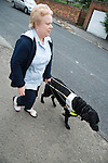 Visually impaired woman walking with guide dog. MR