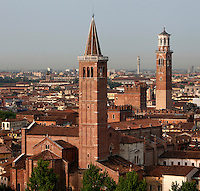 High angle view of the Basilica of Saint Anastasia, c.1290-1400, by the Dominican friars Fra' Benvenuto da Imola and Fra' Nicola da Imola, Verona, Italy, with the Torre dei Lamberti (Lamberti Tower), 12th century, behind, and the city stetching out towards the skyline in the background.  The brick built Sant'Anastasia is Italian Gothic in style. It was restored 1878-81. Construction of the 84 metre high brick, tuff brick and marble Lamberti Tower began in 1172. Lightening knocked off the top of the tower in 1403, and it was restored and raised from 1448 to 1463-64. Picture by Manuel Cohen.