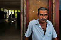 "A Cuban man sits in front of the apartment block in Abel Santamaría, a public housing suburb of Santiago de Cuba, Cuba, 31 July 2008. The Cuban economic transformation (after the revolution in 1959) has changed the housing status in Cuba from a consumer commodity into a social right. In 1970s, to overcome the serious housing shortage, the Cuban state took over the Soviet Union concept of social housing. Using prefabricated panel factories, donated to Cuba by Soviets, huge public housing complexes have risen in the outskirts of Cuban towns. Although these mass housing settlements provided habitation to many families, they often lack infrastructure, culture, shops, services and well-maintained public spaces. Many local residents have no feeling of belonging and inspite of living on a tropical island, they claim to be ""living in Siberia""."