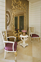 A luxurious mansion dazzles with gilded details and abundant use of marble. In the lobby stand a mirror, armchairs and round table with complex<br />