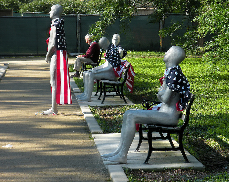 """Tourist wander between the cast iron and aluminum statues of the """"Borders"""" public art exhibit on Michigan Avenue Thursday, July 3, 2014, after unknown artists adorned the pieces overnight with American flags. The Grant Park art installation is by artist Steinunn Thórarinsdóttir (CQ).(DePaul University/Jamie Moncrief)"""