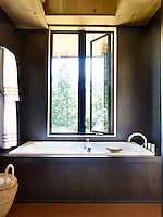 In the master bathroom, the tub is by Kohler and the fittings are by Grohe; the walls are laquered oak veneer and the ceiling is natural pine