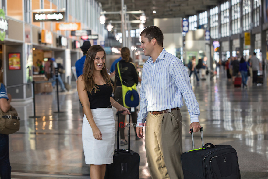 Beautiful business couple smiling while waiting for flight at Passengers wait for rides at the passenger drop off level, Austin–Bergstrom International Airport (ABIA) - Stock Image terminal.