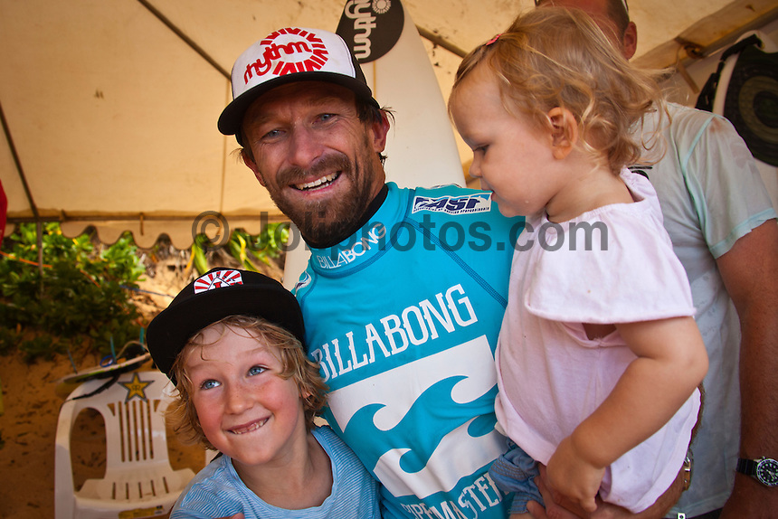 BANZAI PIPELINE, Oahu/Hawaii (Saturday, December 10, 2011) – Kieren Perrow (AUS), with son Tosh and Frankie , has won his inaugural ASP World Tour event, taking out the Billabong Pipe Masters in Memory of Andy Irons over fellow countrymen Joel Parkinson (AUS), 30, in four-to-six foot waves. John John Florence (HAW), 19, also found his way to the podium as the overall winner of the 2011 Vans Triple Crown...Perrow, who finished runner-up to Jeremy Flores (FRA), 23, in last year's Billabong Pipe Masters, returned to form again this year and charged the massive Pipeline conditions on the opening two days of competition to solidify his position on the 2012 ASP World Tour. The Australian was equally deadly in the smaller conditions on the final day and commanded the Final against Parkinson in a backdoor shootout to secure his maiden ASP World Tour victory...John John Florence put on an amazing show at this year's Billabong Pipe Masters, taking the event's only two perfect 10-point rides,  but fell to Slater in the Quarterfinals. Florence's overall effort including a win at the Vans World Cup of Surfing at Sunset Beach and a 5th place at the Reef Hawaiian Pro secured his first Vans Triple Crown win, making him the youngest competitor in history to win the prestigious series.  Photo: joliphotos.com