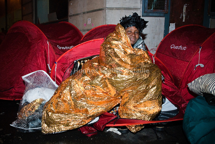 Wrapped in a survival blanket under the rain, a woman is waiting by her tent. Despite the relative comfort they offer, after the first evacuations by the police, some people became scared to sleep inside the tents where they felt trapped.