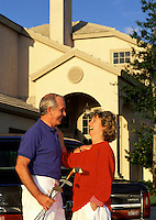 A smiling mature couple laugh and talk outside of their house.