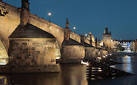 The Charles Bridge or Karluv most in the evening, built 1357 - 15th century, looking towards the Old Town bridge tower from the Vltava river in Prague, Czech Republic. Its construction began under King Charles IV, replacing the old Judith Bridge built 1158'??1172 after flood damage in 1342. This new bridge was originally called the Stone Bridge (Kamenny most) or the Prague Bridge (Prazsky most) but has been the Charles Bridge since 1870. The bridge is 621m long and nearly 10m wide, resting on 16 arches shielded by ice guards, seen here. It is protected by three bridge towers, two on the Lesser Quarter side and one on the Old Town side. The historic centre of Prague was declared a UNESCO World Heritage Site in 1992. Picture by Manuel Cohen