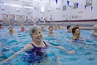 Smiling Senior Citizens exercising at their aquatics class