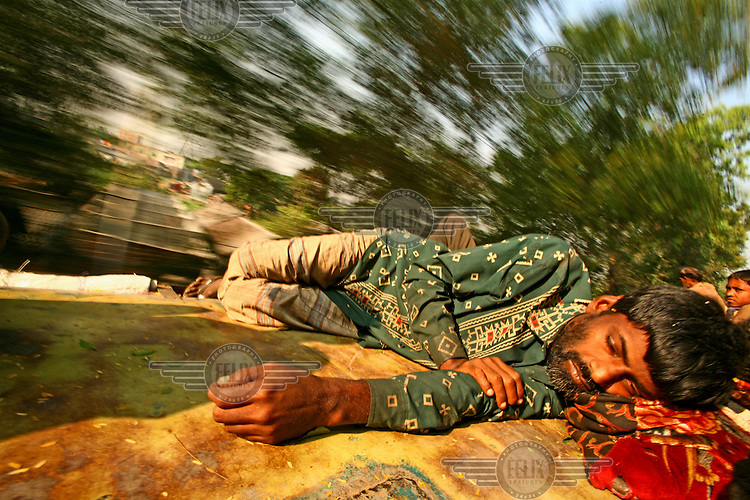 A man travels to the plastic factory where he works. Frequent travellers on train roofs have perfected the art to such an extent that even deep sleep is no problem during the commute.