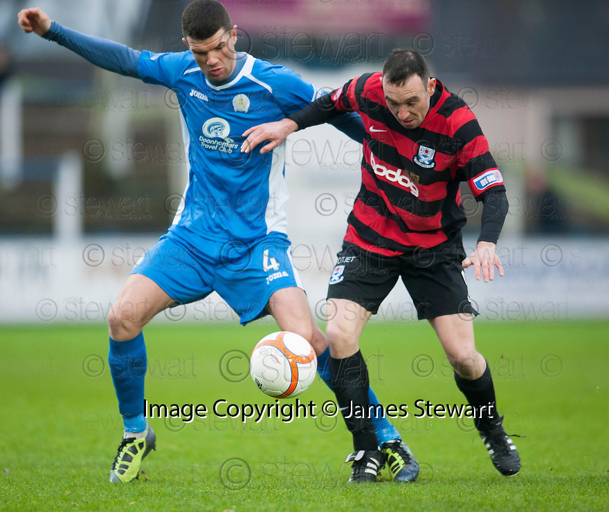Queen of the South's Mark Durnan and Ayr Utd's Michael Moffat challenge for the ball.