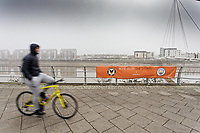 Pictured: A man cycles past a banner by river Usk in Newport, Wales, UK. Thursday 14 February 209<br /> Re: The city of Newport is preparing to host the FA Cup match between Newport County and Manchester City at Rodney Parade, Newport, Wales, UK.