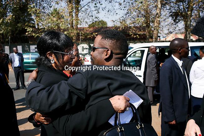 Winnie Mandela hugs Dali Tambo after a funeral memorial service in Soweto.